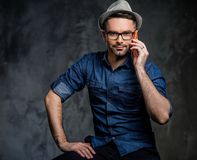 Well-groomed handsome man with hat posing on dark  background. Royalty Free Stock Image