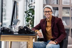 Well-groomed nifty smiling gentleman sitting at desk with typewriters. Desk with typewriters.. Well-groomed nifty brown-haired smiling 30 years old gentleman in royalty free stock images
