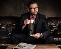 Well-groomed stylish young man  with cup of coffee sitting on comfortable leather sofa on dark background. Stock Photo