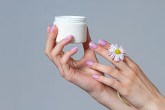 Well-groomed women`s hands with a jar of cream. Stock Photo