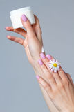 Well-groomed women`s hands with a jar of cream. Royalty Free Stock Photography