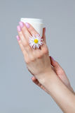 Well-groomed women`s hands with a jar of cream. Royalty Free Stock Images