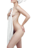 Well-groomed young woman after bath with a towel on white background. Perfect Body. Royalty Free Stock Photo