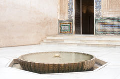 Well head and fountain in a courtyard. In the Alhambra Palace in Grenada, Andalusia, Spain with an ornate entrance door in the background Stock Image