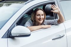 Well hi! Happiness business woman in a car, looking at camera an. D send hello sign. Outdoor photo, auto and safety concept Stock Photos