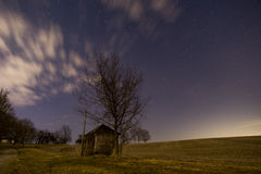 Well-House in a Field. The night sky over an old well-house and harvested field royalty free stock photography