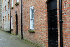 Well-kept brick and stone buildings on cobblestone walkway Stock Photos