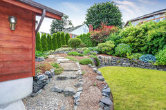 Well kept garden near the house with wooden trim. Nice landscape design. Stock Photos