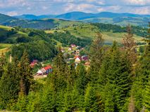 Well-kept houses lurking on mountain slopes hidden by green trees. For your design royalty free stock photography