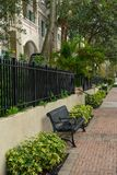 Well kept sidewalk in Fort Lauderdale. The well kept sidewalk along West Las Olas Blvd in Fort Lauderdale Florida with black wrought iron railing and benches royalty free stock photos