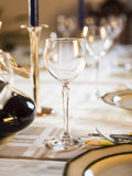 Well-laid Table. A table with wine glasses, dishes and plates for a celebration stock image