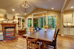 Well lit dinning room with connected living room. Stock Images