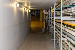 A well lit Maintenance Hallway in an industrial building with conduit running down the side. Providing power royalty free stock photo