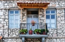 Well Maintained Greek Village Stone House, Greece. A well preserved and maintained Greek Village stone house, with flower pots on balcony and duck egg blue royalty free stock photography