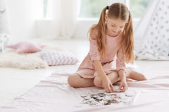 Well mannered kid playing puzzle game. Smart activity. Adorable girl with ponytails sitting on the floor and sorting puzzle pieces while playing at home Stock Image