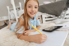 Well mannered schoolgirl creating new masterpiece in notebook. Talented youngster. Pretty little girl looking into the camera and smiling while lying on the Stock Photo