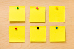 Well Ordered Yellow Post-it Collection. Set of six well-ordered square yellow blank post-it notes affixed by colored pins on a wooden board and ready to take a Stock Photography