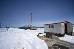 Well pad in the winter. Winter landscape with oil derrick stock photo