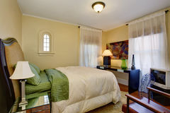 Well put together bedroom with green and white bedding. Royalty Free Stock Image