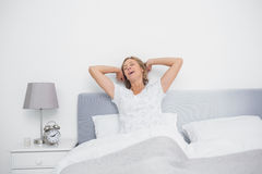 Well rested blonde woman stretching and yawning in bed. In bedroom at home Stock Photography