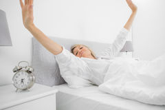 Well rested woman waking up and stetching. At home in bed Stock Photos