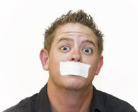Well, Shut My Mouth. Early 20s man mug shot with wide eyes and a piece of tape over his mouth. White background stock image