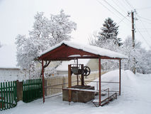 Well in small rural street. Snow-covered well in small rural street Stock Photography