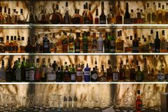 Well stocked bar with various alcoholic bottles and glasses stock photography