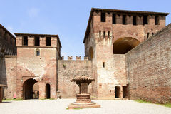 Well and towers, Soncino Castle. View of the well and of one of the massive towers from main inner court in the ancient Sforzesco Castle, shot in bright summer royalty free stock photography