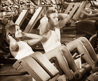 Well trained glad young man and woman training abdominal muscles Royalty Free Stock Photo