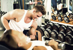 Well trained man training hands using heavy weight dumbbells in Stock Images