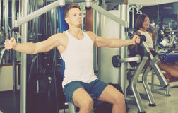 Well trained man using pec deck gym machinery indoors. Young well trained men using pec deck gym machinery indoors Stock Image