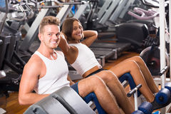 Well trained smiling young man and woman training abdominal musc Royalty Free Stock Photography