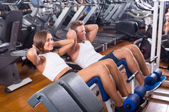 Well trained young man and woman training abdominal muscles in g Stock Images