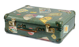 Well travelled old vintage suitcase. Covered in a variety of colorful labels depicting worldwide tourist destinations visited on vacation, isolated on white Stock Photography