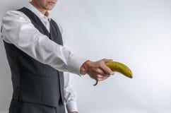 Well ubierający mężczyzna trzyma banana jak pistolet w kostium kamizelce zdjęcia stock