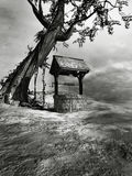 Well under a creepy tree. Gothic scene with lonely tree and old well Royalty Free Stock Photography