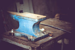 Well-used blue anvil from metal foundry workshop. Well used blue anvil from metal foundry workshop positioned on table with metal rod in background Stock Photo