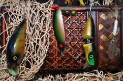 Catch the Big Fish with a Good Lure. Fishing lures and a gray netting hanging from a brown weaved basket close-up Royalty Free Stock Photography