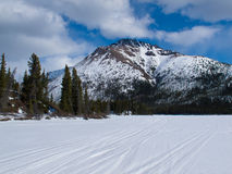 Well used winter trail on frozen mountain lake Stock Photography