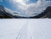 Well used winter trail on frozen mountain lake Stock Images