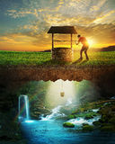 Well and water. A man lowers a bucket from a well into clear water stock photography