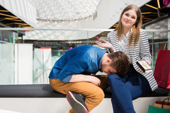 Well, what can I do?. A photo of young couple sitting on the bench at the mall. The girl is shrugging her shoulders with innocent face, and her boyfriend seems Royalty Free Stock Image