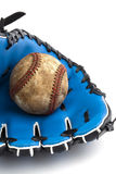Well worn baseball and a leather glove Stock Photo