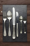 Well-worn cutlery on slate Stock Photo