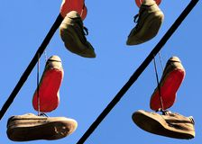 Well worn sport shoes hanging from power line Royalty Free Stock Photo
