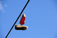 Well worn tennis shoes hanging from power line Stock Image