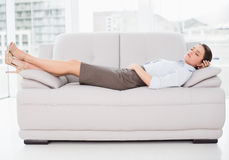 Well young woman sleeping on sofa at home. Side view of a well dressed young woman sleeping on sofa at home Royalty Free Stock Images