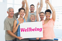 Wellbeing against grey wall. The word wellbeing and portrait of happy fit people holding blank board against grey wall Royalty Free Stock Image