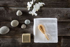 Wellbeing still life for detox spa with cleansing loofah brush. Pure white towel and orchids and beautiful pebbles on genuine old wood background, flat lay Stock Photo